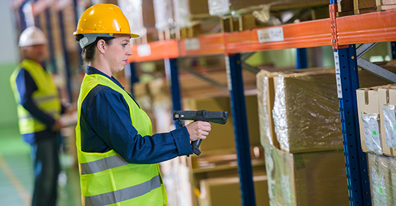 Female warehouse employee scans informations from boxes loaded on pallets stored in pallet racks in the warehouse.